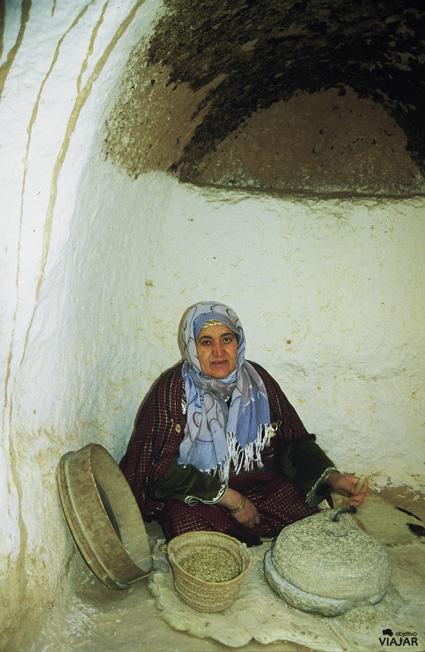 Mujer moliendo trigo en una casa troglodita de Matmata. Túnez